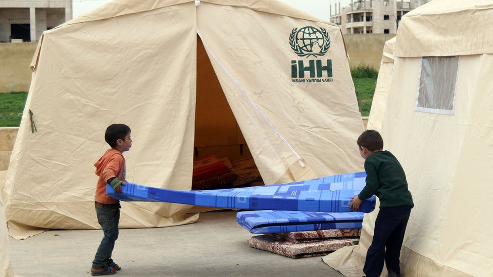 Children carry a mattress outside a tent erected in the rebel-held Syrian city of Idlib (12 April 2017)