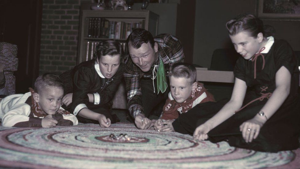 American actor and singer Roy Rogers (1911 - 1998) playing marbles with his children in the family living room, circa 1955. From left to right, Sandy, Marion Fleming (his foster daughter), Roy Rogers, Roy Jr. aka Dusty, and Linda Lou. (Photo by Archive Photos/Getty Images)