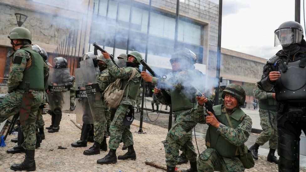 Security forces aim weapons at the entrance of the National Assembly building, in Quito, Ecuador, October 8