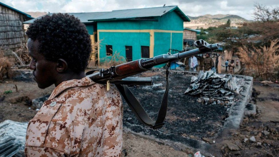 A member of the Afar Special Forces holds a gun next to a damaged house in the village of Bisober in Ethiopia's Tigray region, on December 9, 2020