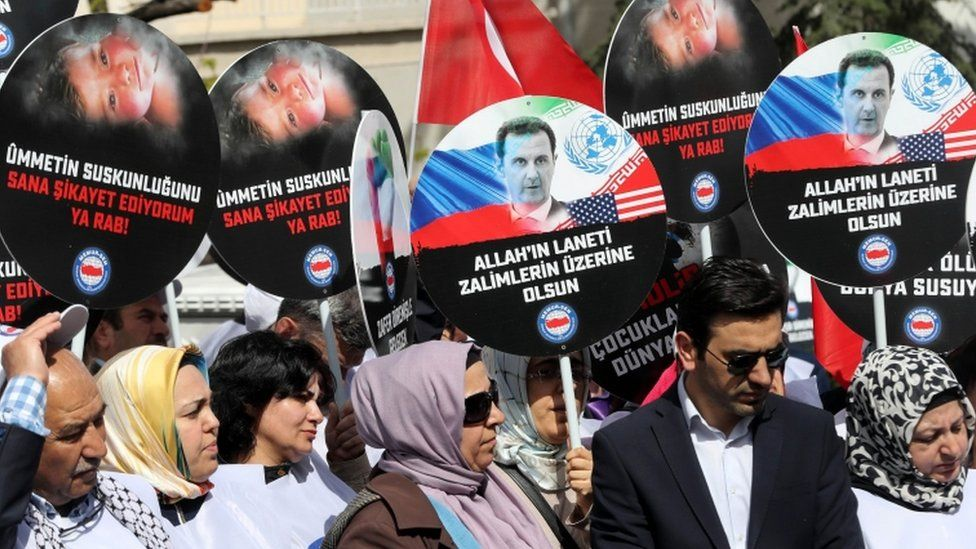People holds placards during a protest against Russia for its alleged role in a chemical attack in the Syrian province of Idlib, on April 7, 2017 in front of the Russian embassy, in Ankara