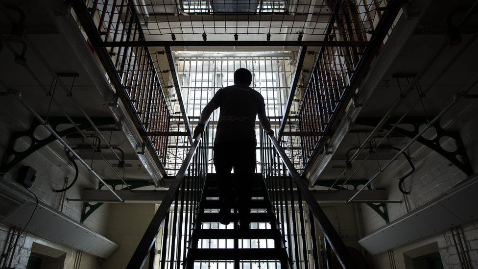 A man walking up stairs in a prison