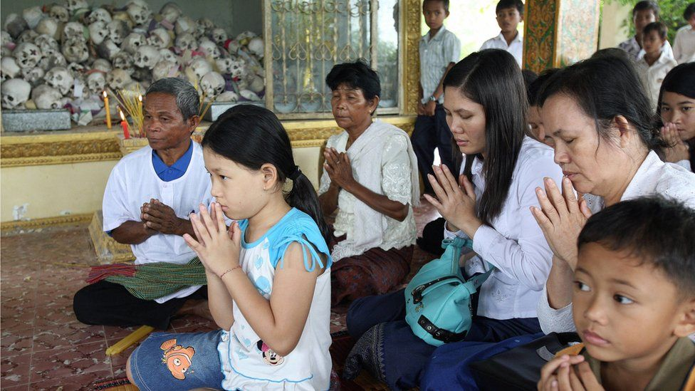 Cambodian people pray to Buddhist monks in front of skulls, at a pagoda in Takeo Province some 35 kilometres south-east of Phnom Penh, 04 October 2007.