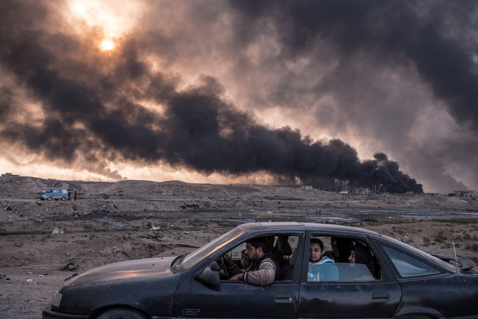 A family flees the fighting in Mosul, Iraq's second-largest city, as oil fields burned in Qayyara, Iraq, on 12 November 2016.