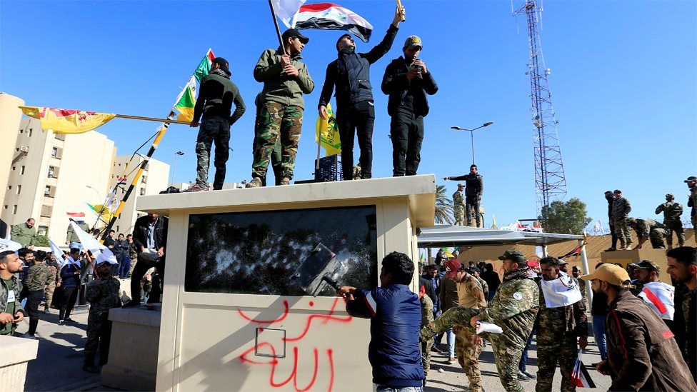 Protesters attack a security post outside the US embassy in Baghdad, Iraq (31 December 2019)