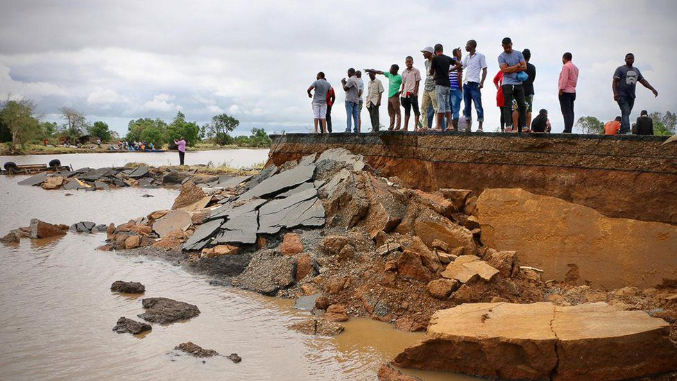 Locals stand beside a damaged section of the road between Beira and Chimoio in Nhamatanda district, central Mozambique
