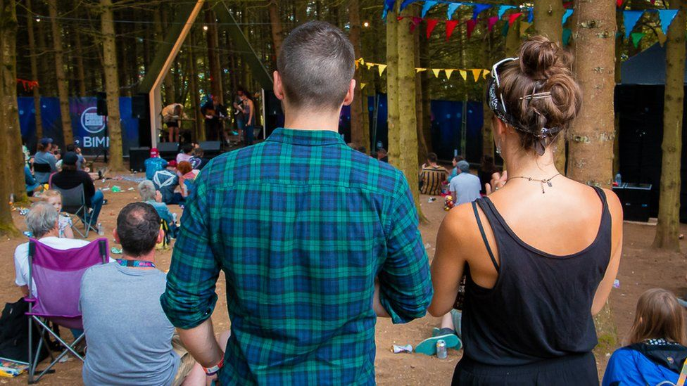 Two friends stand together at a festival