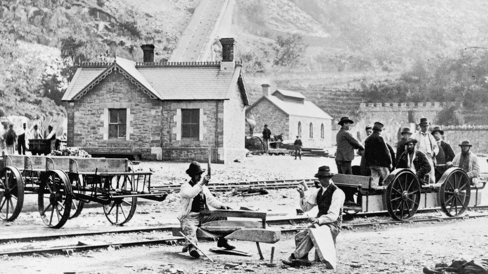 Photo of quarrymen cutting slate and using a pedal-powered truck at Llanberis around 1880