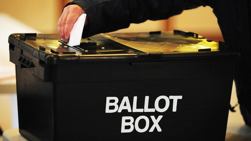 A voter puts a ballot paper into a ballot box