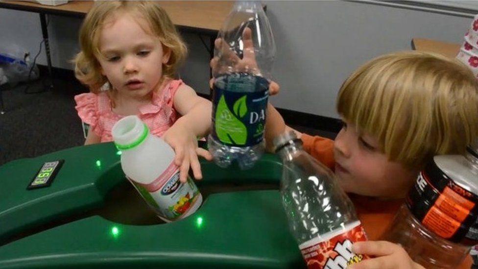 Kids putting plastic bottles into a smart bin