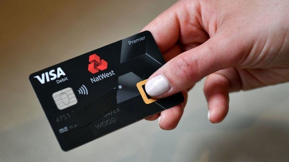 An employee poses with UK's first biometric fingerprint debit card during a photocall at Natwest offices in central London on April 24, 2019.