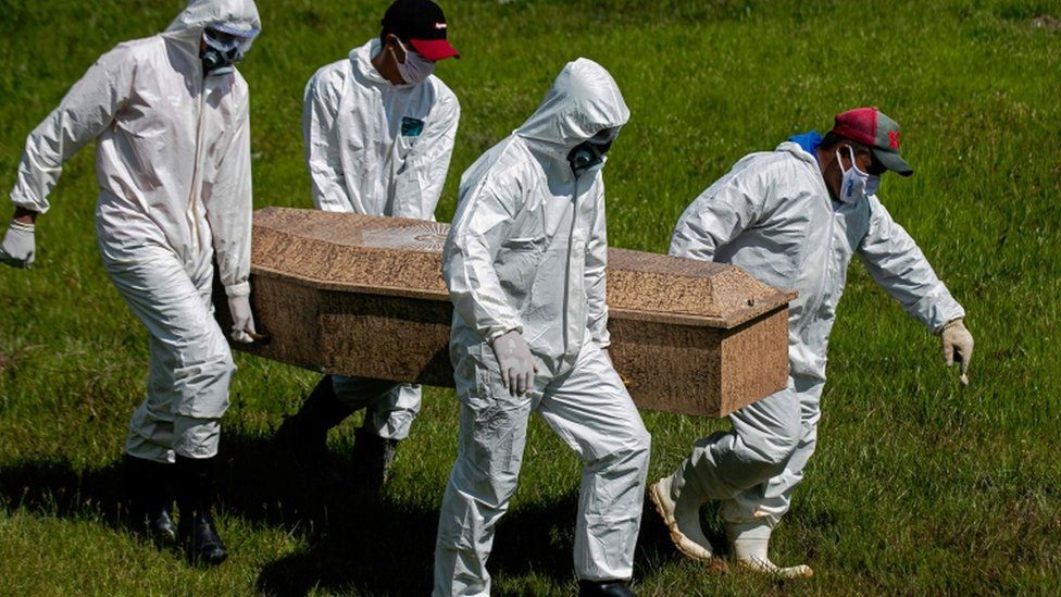 Cemetery workers wear protective suits as they carry out a burial
