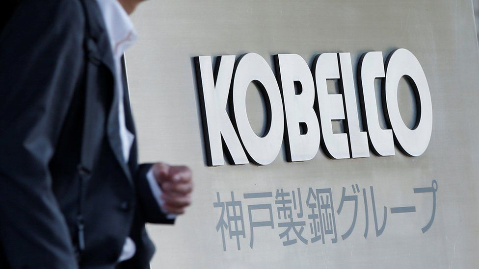 A man walks past the company name on a sign