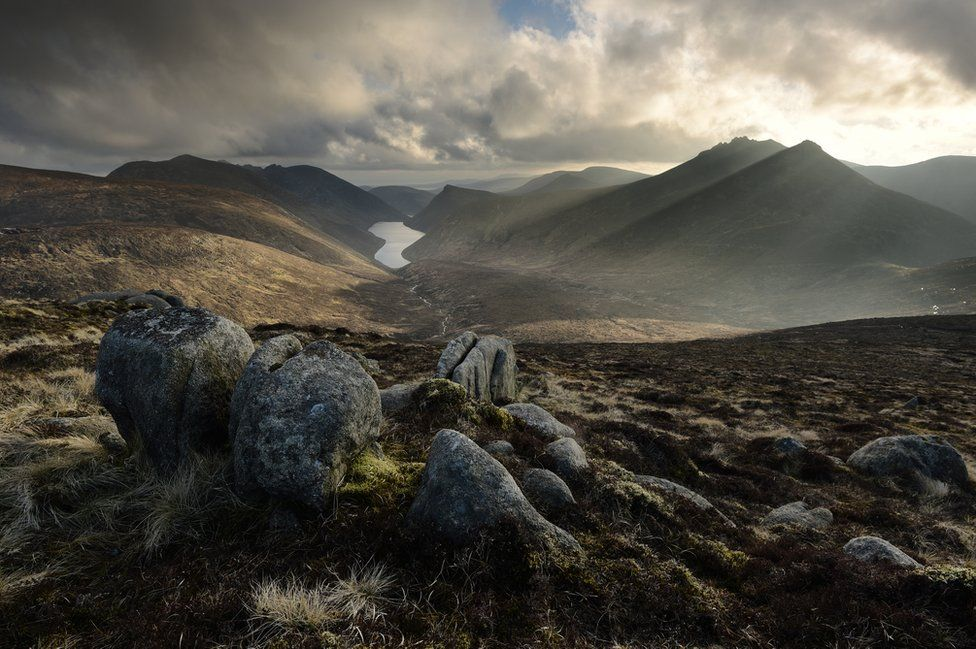 Stones sit in the foreground of a valley with light streaming through