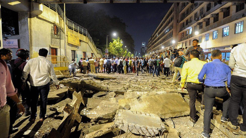 People help move debris after a bridge collapse in Mumbai