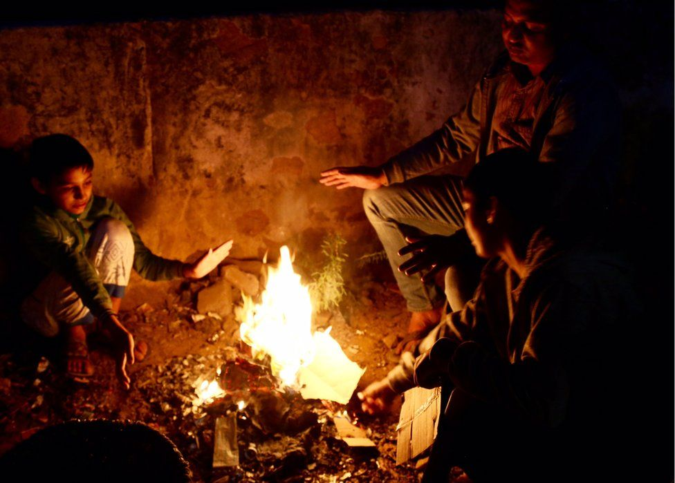 Three people hold their hands up to a campfire for warmth