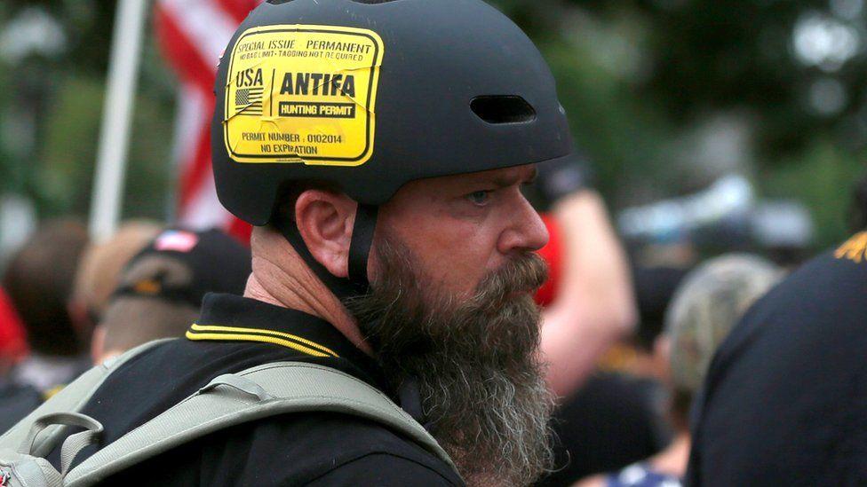"A man wears a sticker that says ""Antifa Hunting Permit"" at a Proud Boys rally in Portland, Oregon, U.S., August 17, 2019."