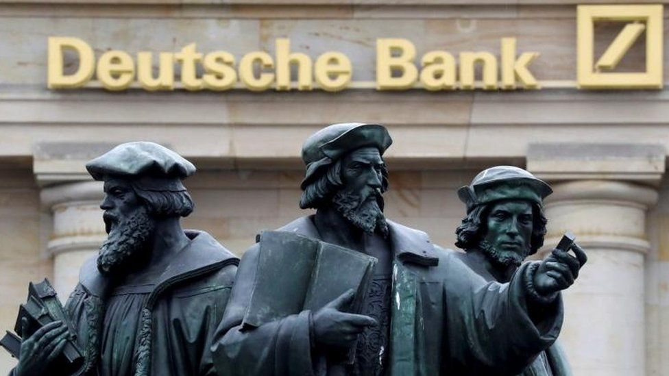 Statues in front of Deutsche Bank sign