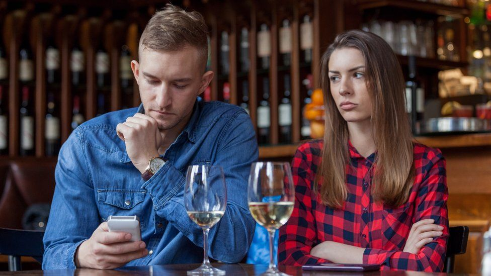 A man on his phone during a meal with his girlfriend