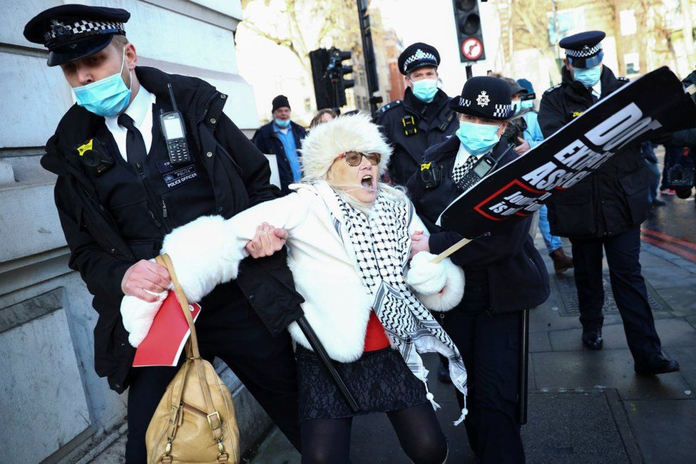 Police officers detain a woman holding a placard outside the Westminster Magistrates Court as Julian Assange's lawyers seek bail for their client in London, 6 January 2021.