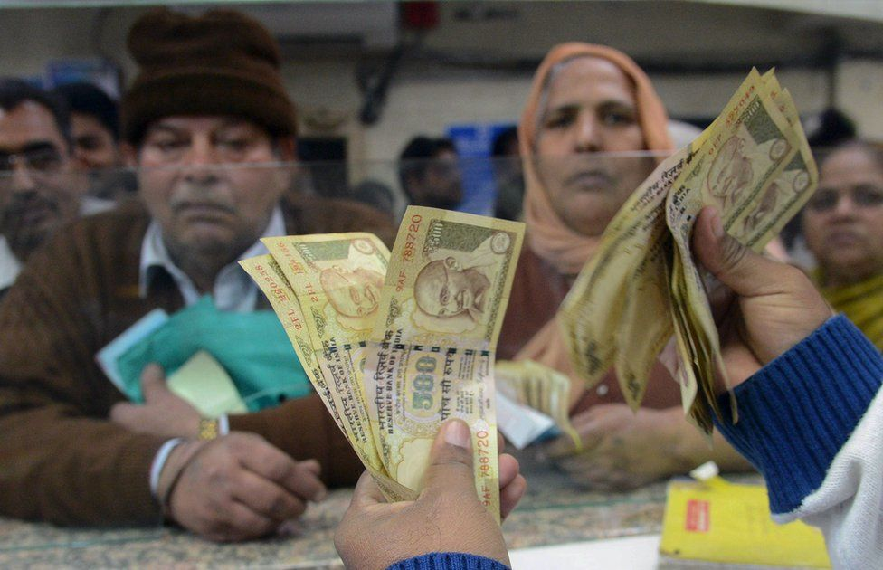 An Indian bank teller counts old notes