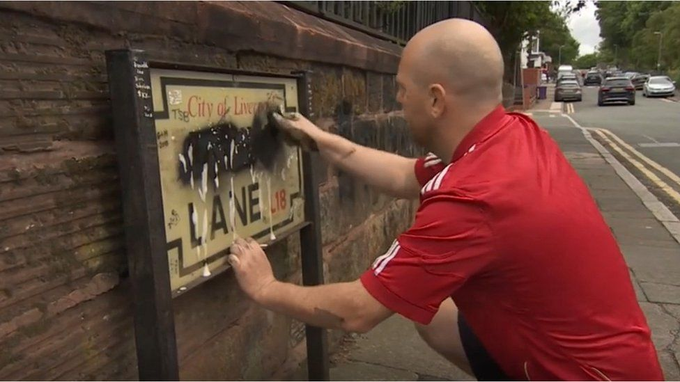 Emmett O'Neill cleaning a Penny Lane sign