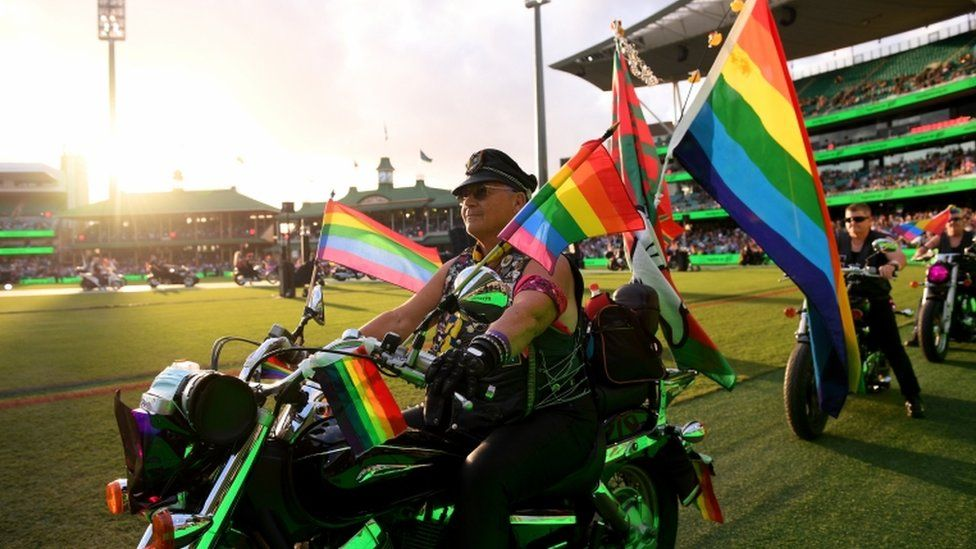 Someone is seen on a motorbike with lots of rainbow flags