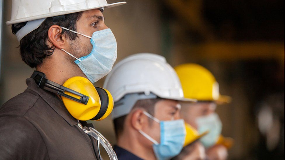 Machine workers wearing face masks