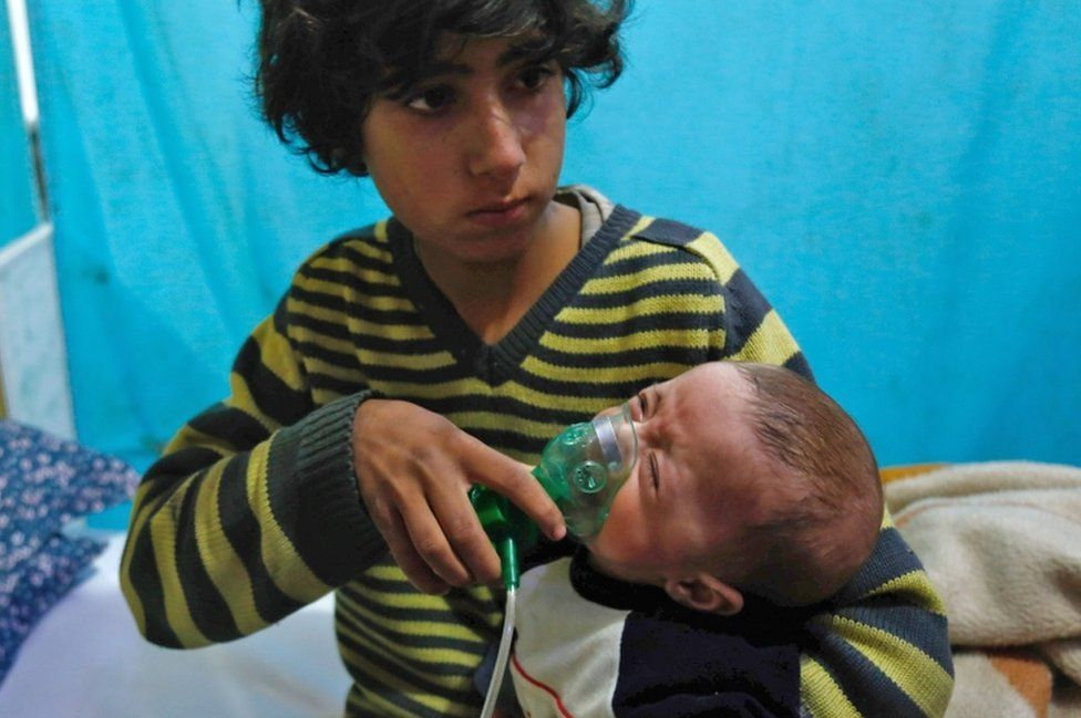 A Syrian boy holds an oxygen mask over the face of an infant at a make-shift hospital following a reported gas attack on the rebel-held besieged town of Douma in the eastern Ghouta region on the outskirts of the capital Damascus on January 22, 2018