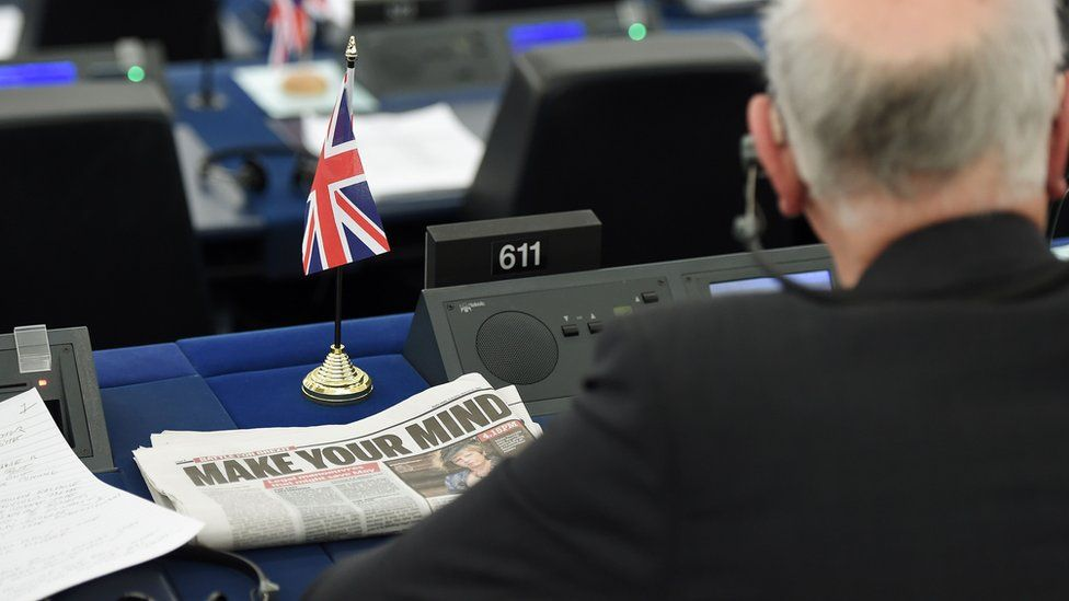 """A newspaper headline shows the words """"make your mind"""" on a British European parliament seat, complete with little UK flag"""