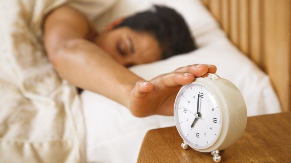 A woman hits an alarm clock