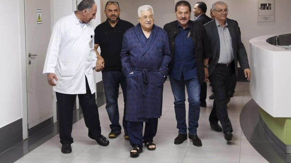 Image released by Mahmoud Abbas's office showing the president (centre) walking in a hospital corridor (21/05/18)