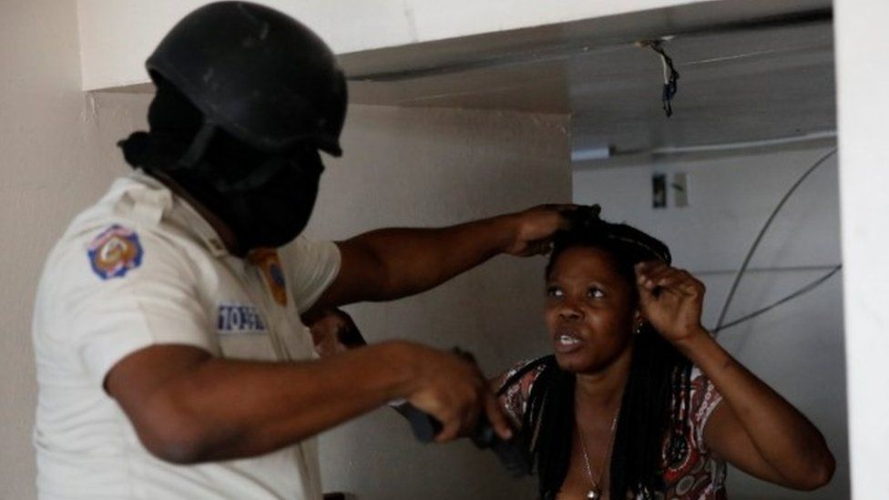 A Haitian National Police officer holds a woman found inside a bank office at a commercial area that was looted during protests against fuel price increases in Port-au-Prince, Haiti, July 8, 2018