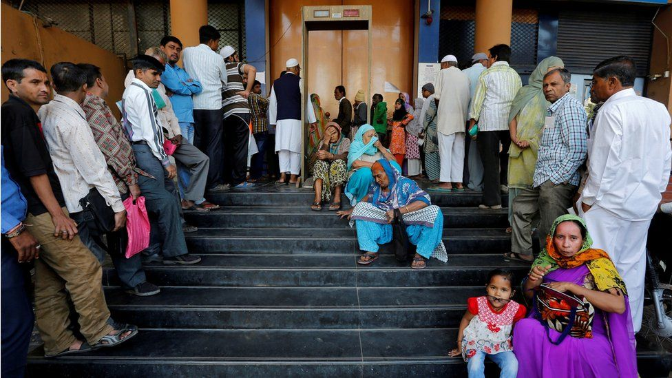People wait for a bank to open to withdraw and deposit their money, after the scrapping of high denomination 500 and 1,000 Indian rupees currency notes, in Ahmedabad, India, December 5, 2016.