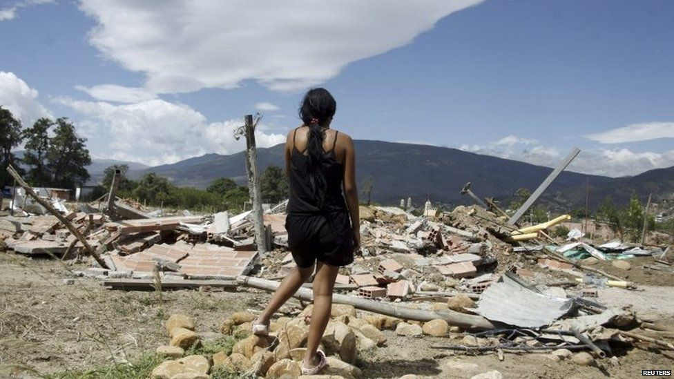 A woman stands in front of the ruins of houses demolished by Venezuelan officials in San Antonio, Venezuela, on 24 August, 2015.