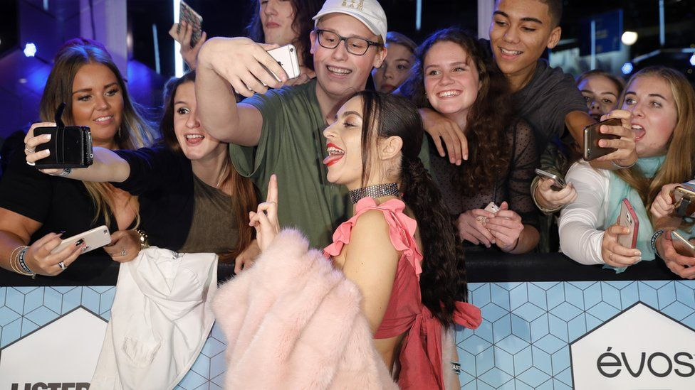 Charli XCX with fans on the red carpet
