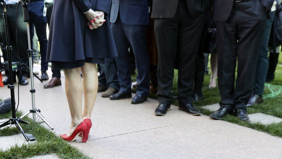 Julie Bishop gives a press conference, with the image framing only her studded red heels against a sea of brogues and dark suits