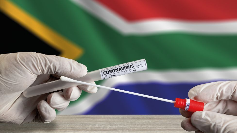 Gloved hands holding a swab coronavirus test in front of the South African flag