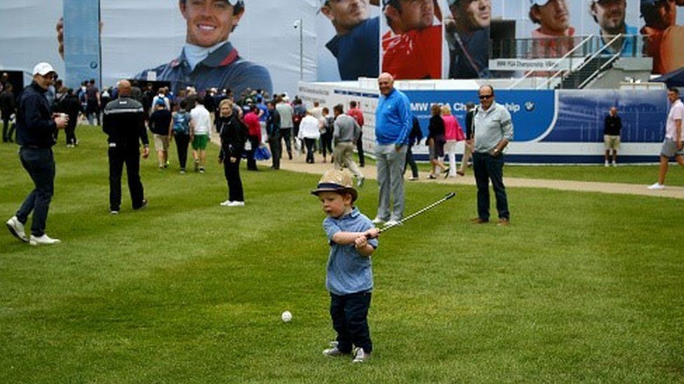 A little boy takes a swing at a golf ball