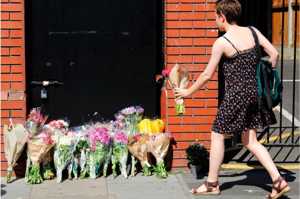 A woman lays flowers in tribute outside Finsbury Park Mosque in the Finsbury Park area of north London