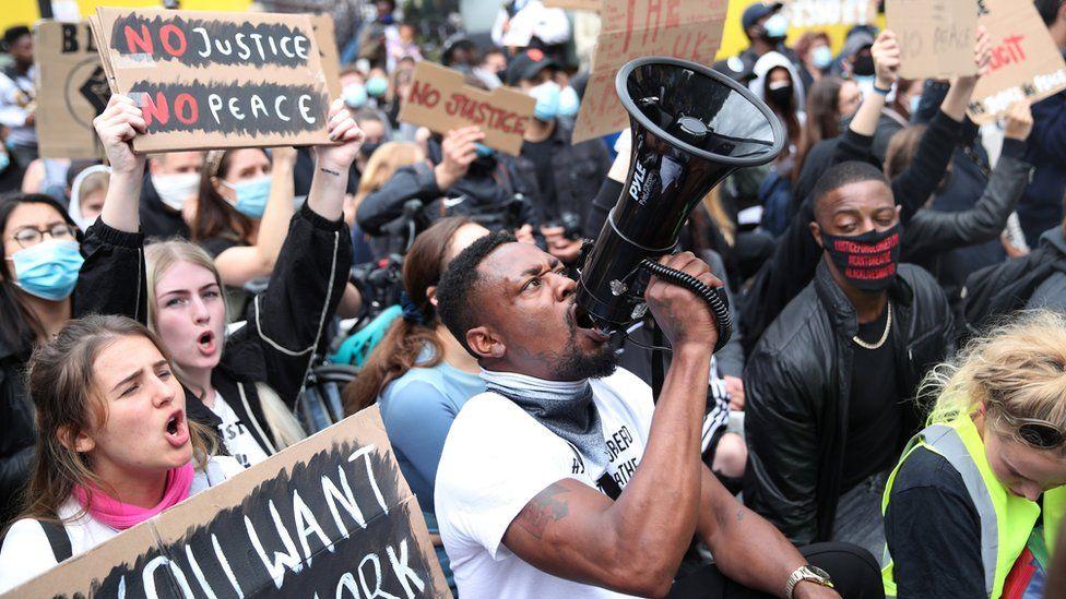 A demonstrator shouts through a megaphone outside London's US embassy