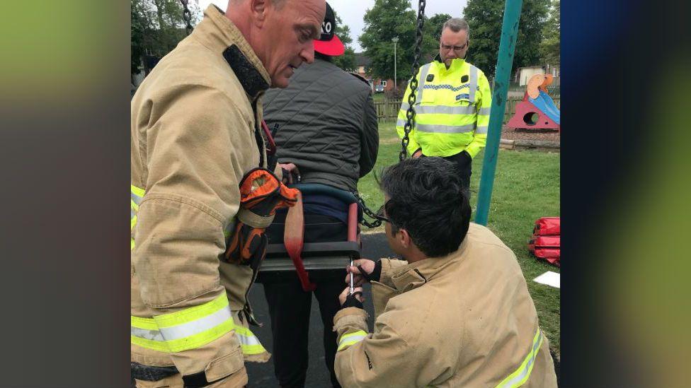 Firefighters releasing man from swing