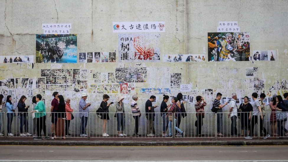 """People queue to cast their vote in front of a """"Lennon Wall"""" adorned with tattered posters"""