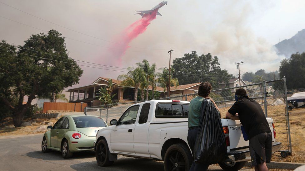 A firefighting aircraft drops fire retardant as the Holy Fire burns near homes on August 10, 2018 in Lake Elsinore, California