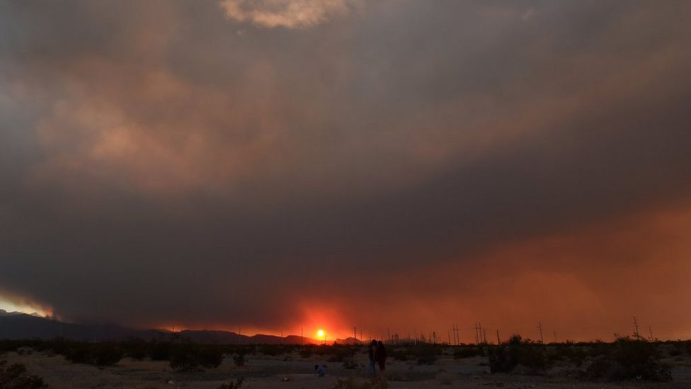 The wildfire obscures the setting sun