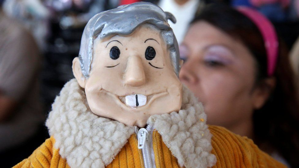A supporter holds a figure of leftist frontrunner Andres Manuel Lopez Obrador as she takes part in his campaign rally