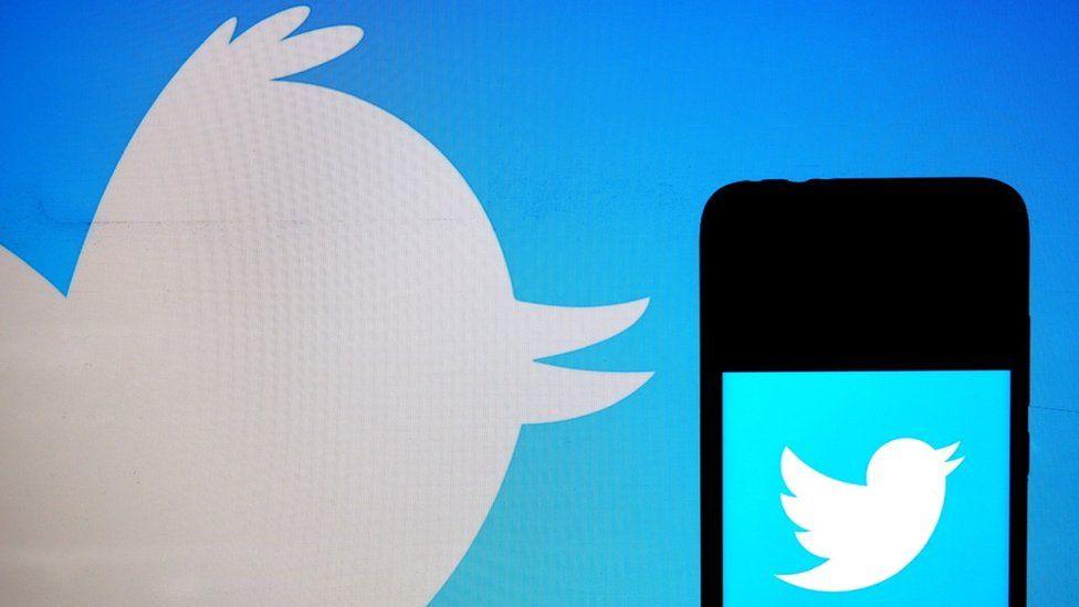 Twitter logo on phone on background of Twitter logo