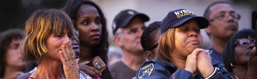 People attend a vigil for the victims of the recent mass shootings