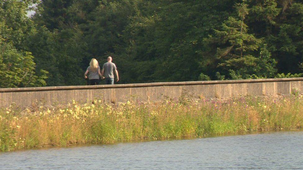 A couple walking along a river