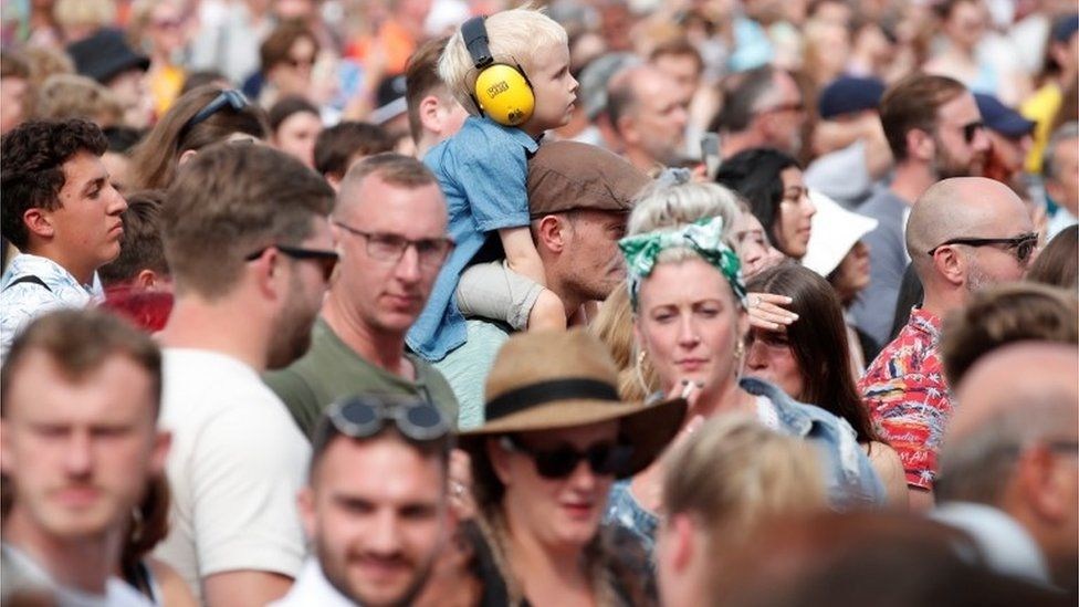 A boy wearing ear defenders as the crowd watch Maisie Peters at Latitude Festival